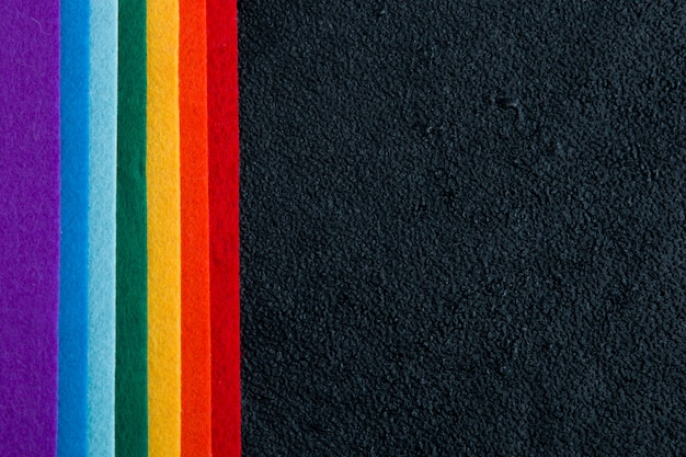 Rainbow felt on a black background top view wet drops of water lgbt symbol