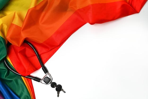 Радужный флаг текстуры ткани для лгбт с металлической цепью и замком на белом фоне. концепция любви и свободы.