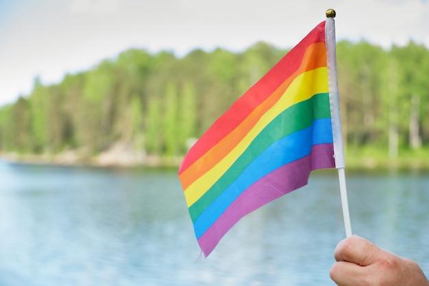 잔디, 호수, 나무 배경에 있는 lgbt 커뮤니티의 무지개 깃발 상징, 여성의 손에 있는 깃발