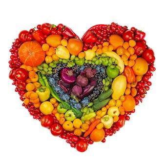 白い背景で隔離の果物と野菜のスタジオの虹の心は菜食主義者の愛の健康的な食事の概念に行きます