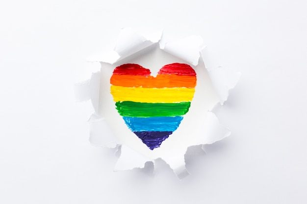 Rainbow heart smashing through layers of white paper