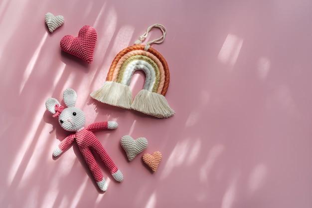 ピンクの背景にレインボーハートとニットバニー。赤ちゃんと子供部屋のためのかわいい装飾とアクセサリー。フラットレイ、上面図
