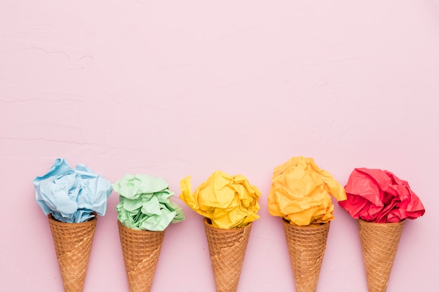 Rainbow ice cream from crumpled colorful paper in waffle cones