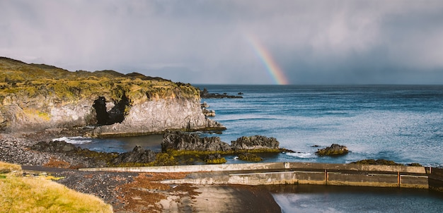 Rainbow over the icelandic coast in the middle of nature.