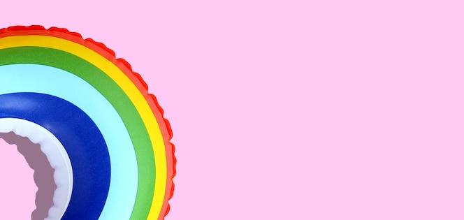 Anello di piscina gonfiabile arcobaleno su sfondo rosa.