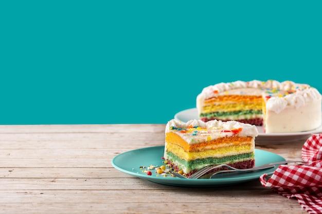 Torta a strati arcobaleno su tavola di legno e sfondo blu