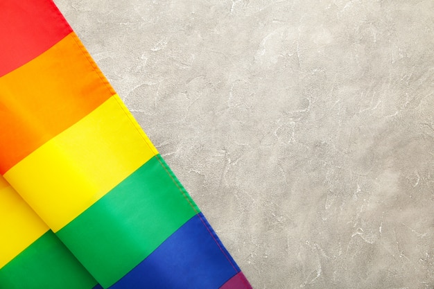 Rainbow lgbt flag on grey concrete background with copy space