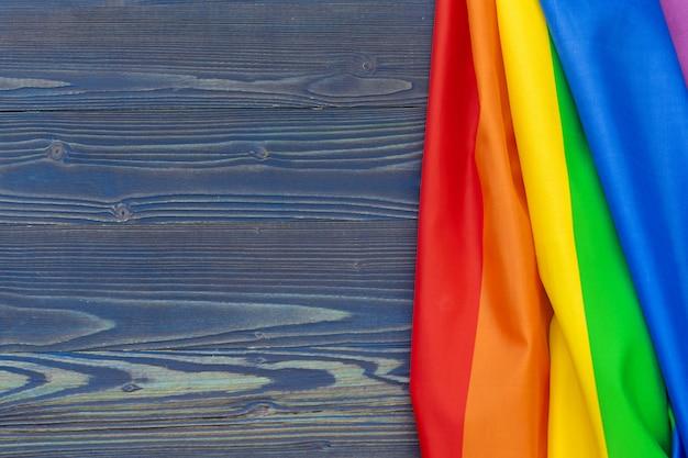 Rainbow lgbt flag on wooden table background