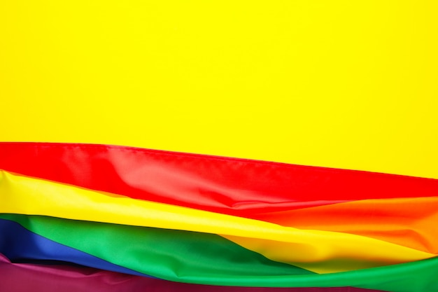 Rainbow lgbt flag on yellow background with copy space