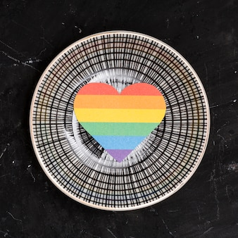 Rainbow lgbt heart on round plate on black background