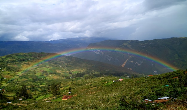 Rainbow over the lower hilltop village, aerial view from kuelap fortress in amazonas region, northern peru
