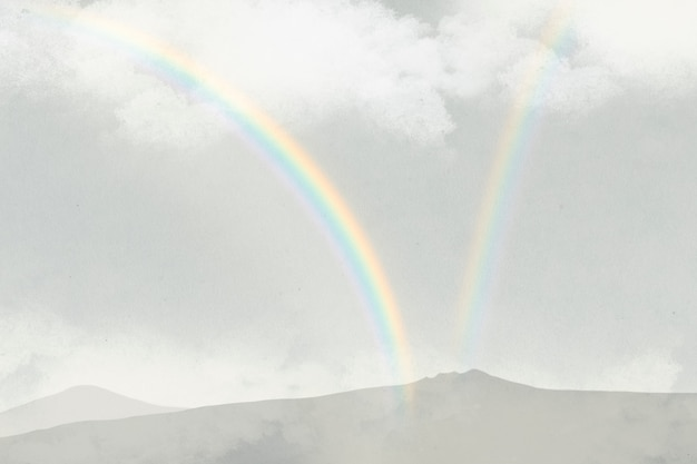 Rainbow over mountains background with clouds