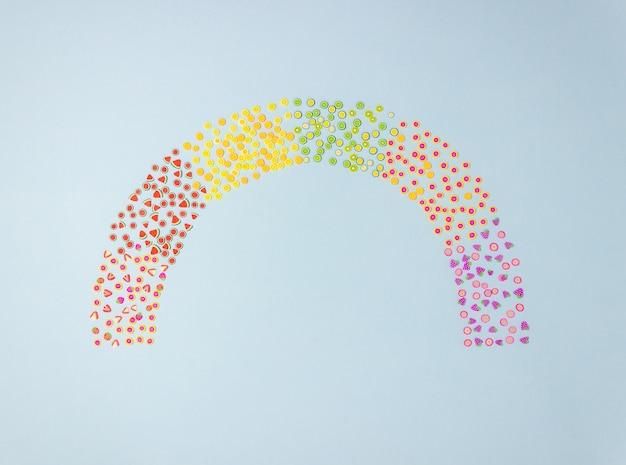 青色の背景におもちゃのフルーツの虹。最小限のコンセプト。独創的なアイデアです