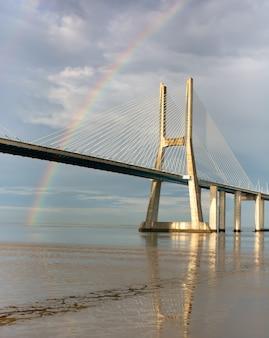 Радуга на мосту васко де гама, лиссабон, португалия