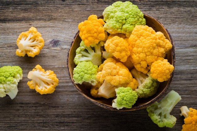 Rainbow of organic cauliflower on the wooden table.