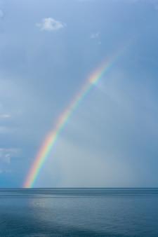 Радуга над озером байкал на фоне дождевых облаков. вертикальное изображение.