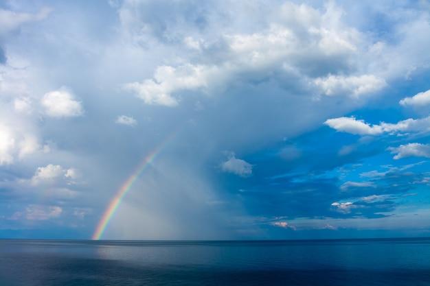 Радуга над озером байкал с дождевыми облаками в небе. горизонтальное изображение.