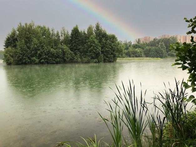 비가 오는 동안 호수 위의 무지개