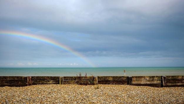 ドーバー英国の小石のビーチの後ろの海の上の虹