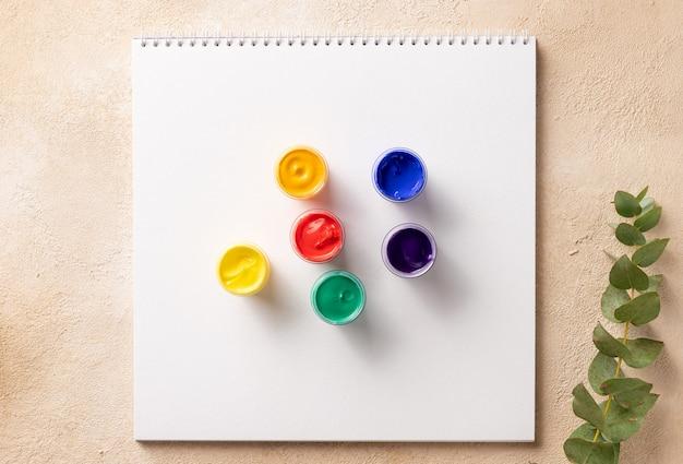 Банки с радужной краской на альбоме для рисования лгбт-концепция цветов