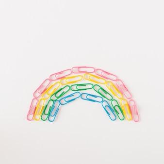 Скрепки радуги расположены полукругом на белом фоне. концепция школы