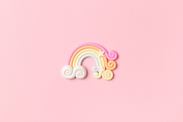 Rainbow pastel color arc on light pink background.