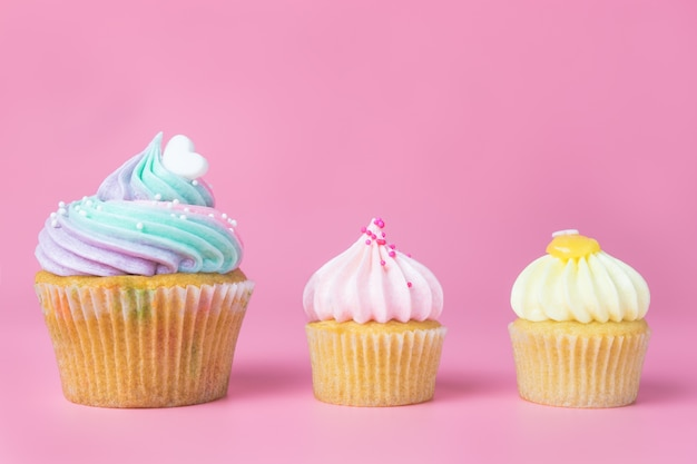 Rainbow pastel cupcakes and mini cupcakes on pink background