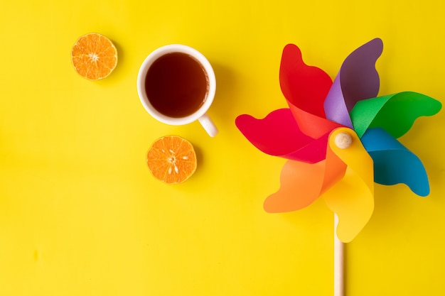 Rainbow pinwheel on yellow with hot drink and sliced orange fruit flat lay