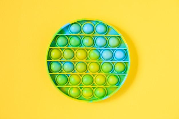 Игрушка-непоседа rainbow pop it на фоне пустой копии пространства