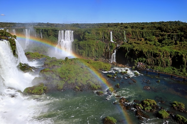 Rainbow over powerful iguazu falls at brazilian side with many visitors on boardwalk, foz do iguacu, brazil