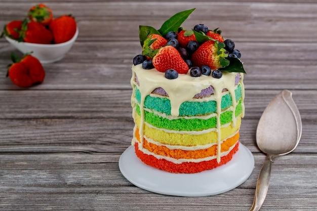 Rainbow sponge cake decorated with fresh berries.