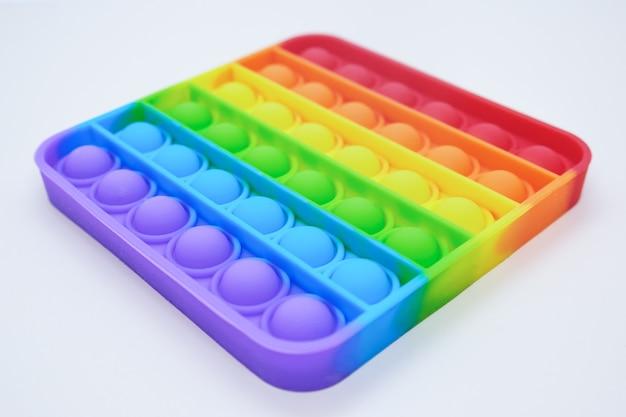 Rainbow square fidget toys pop-it на светлом фоне. нажмите pop bubble. популярная расслабляющая силиконовая игрушка для снятия напряжения квадратной формы. вид под углом в перспективе.