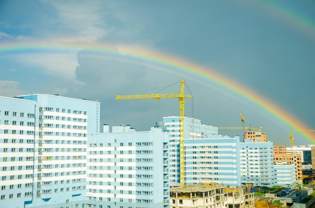 The rainbow stretches over the highrise buildings of the city