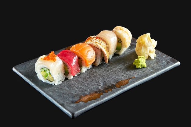 Rainbow sushi roll with different types of seafood: salmon, eel, shrimp, scallop, tuna and avocado, served on a ceramic plate with ginger and wasabi. isolated on a black background. japanese food
