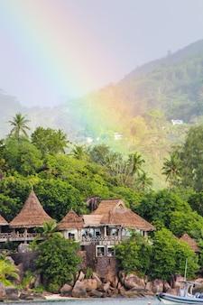 Rainbow over tropical island and luxurious hotel