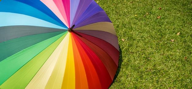 Rainbow umbrella in grass field vintage and retro tone, soft focus