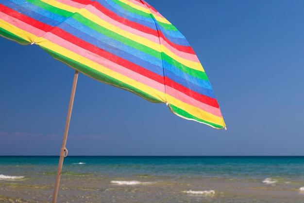 Радужный зонт на пляже против голубого неба греция остров тасос