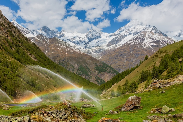 서머 알프스 산 (스위스, 체르마트 근처)에서 관개 용수에 무지개가 솟아납니다.
