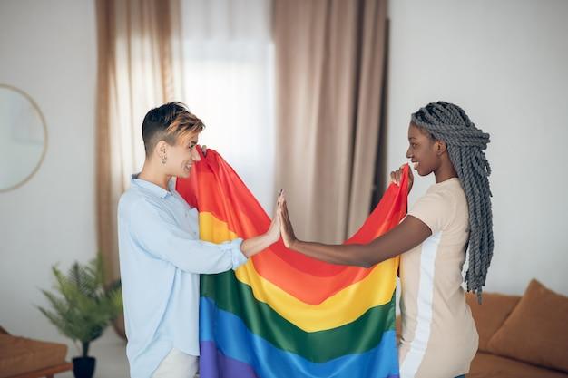 レインボックスフラグ。虹色の旗を持って幸せそうに見える2人の若い女の子
