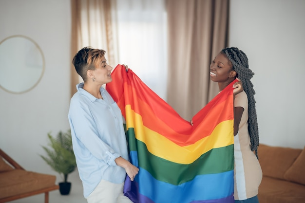 Rainbox flag. two young girls holding a rainbow flag and looking happy