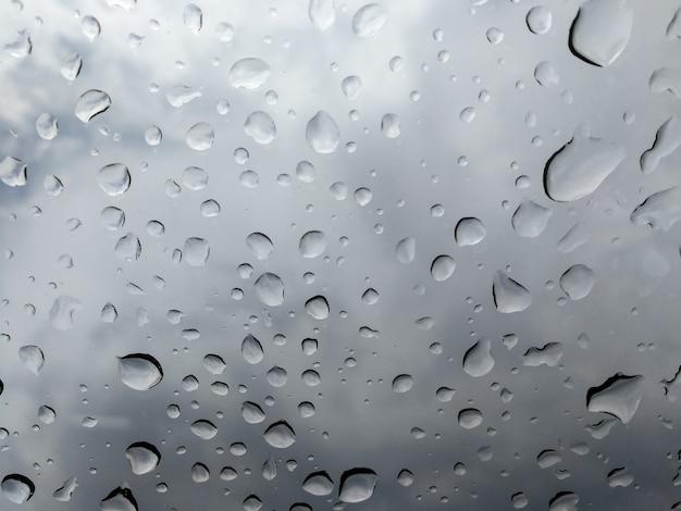Raindrop falling on the window glass car.