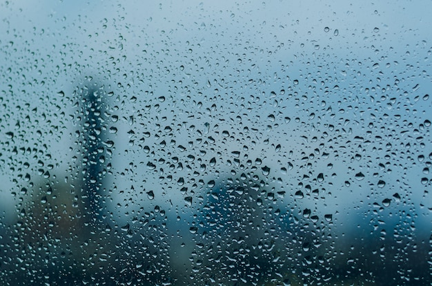 Raindrop on glass window in monsoon season with blurred city background