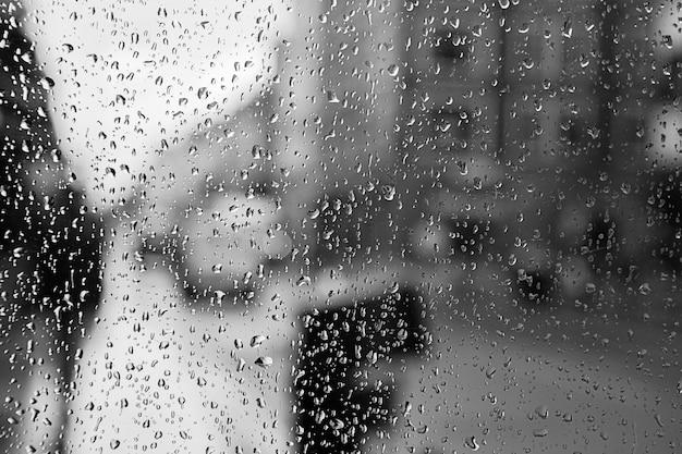 ガラスの雨滴とロンドンのバスのライトがぼやけている