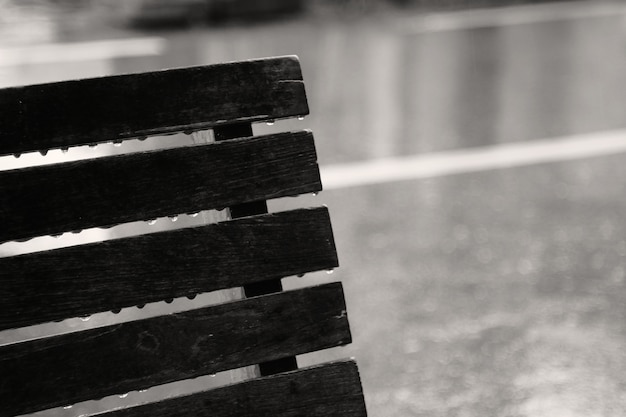 Raindrops on bench on a rainy day. concept of lonely, sad, alone.