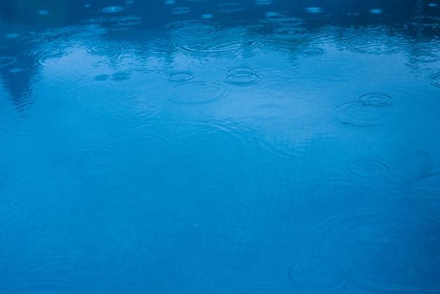 Raindrops falling on a pool or blue lake
