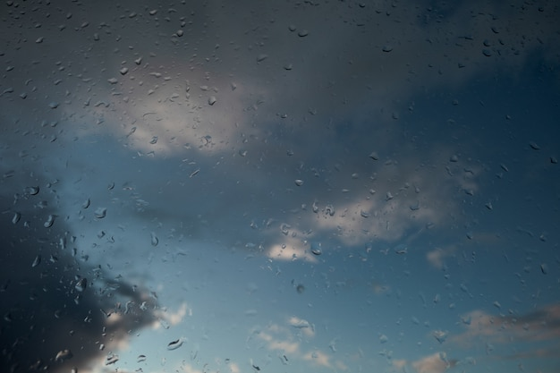 Raindrops on glass. the sky in the background Premium Photo