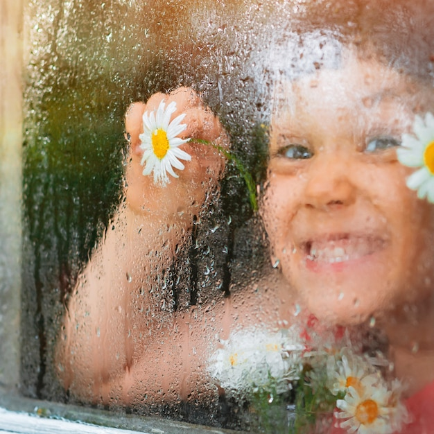Raindrops on the glass of a village window, chamomile flowers eyes in children's hands look at the rain.