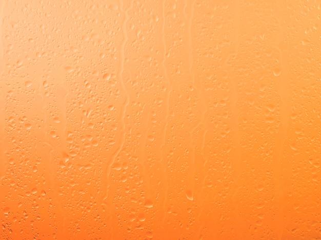 Raindrops on glass window pane surface over vivid orange sunset sky