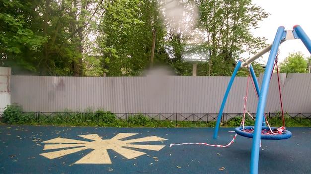 렌즈에 빗방울입니다. 전염병 또는 전염병으로 인해 놀이터가 폐쇄되었습니다. 비와 악천후의 울타리 놀이터. 자가 격리 모드. 집에 있어!