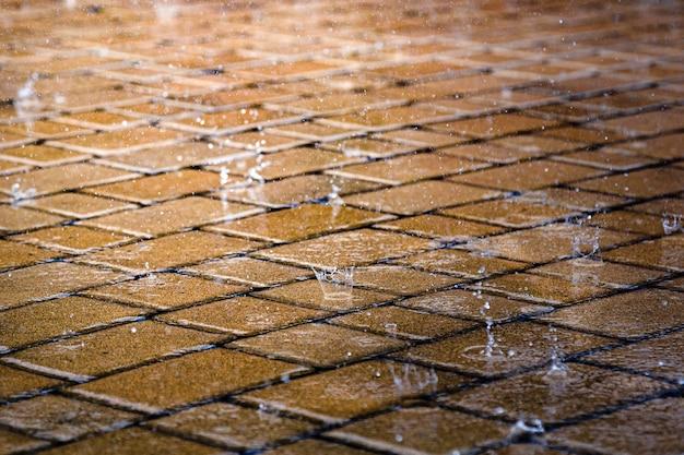 거리에 빗방울이 비가 동안 도시에서 젖은 바닥 타일. 비오는 날에 도시 보도.